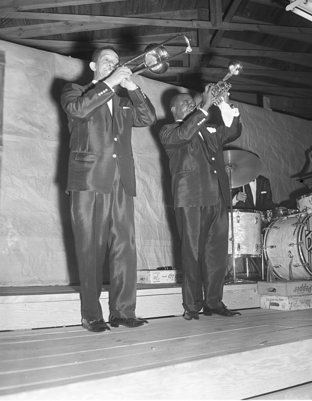 Louis Armstrong playing trumpet with man